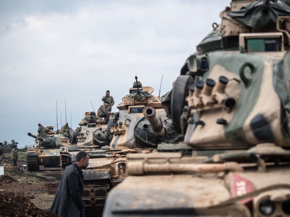 Turkish army tanks gather close to the Syrian border on Sunday. (BULENT KILIC/AFP/Getty Images)