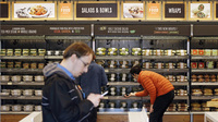 Shoppers roam through an Amazon Go store in April. The automated grocery, which had been restricted to Amazon employees, will now be open to the general public starting Monday.