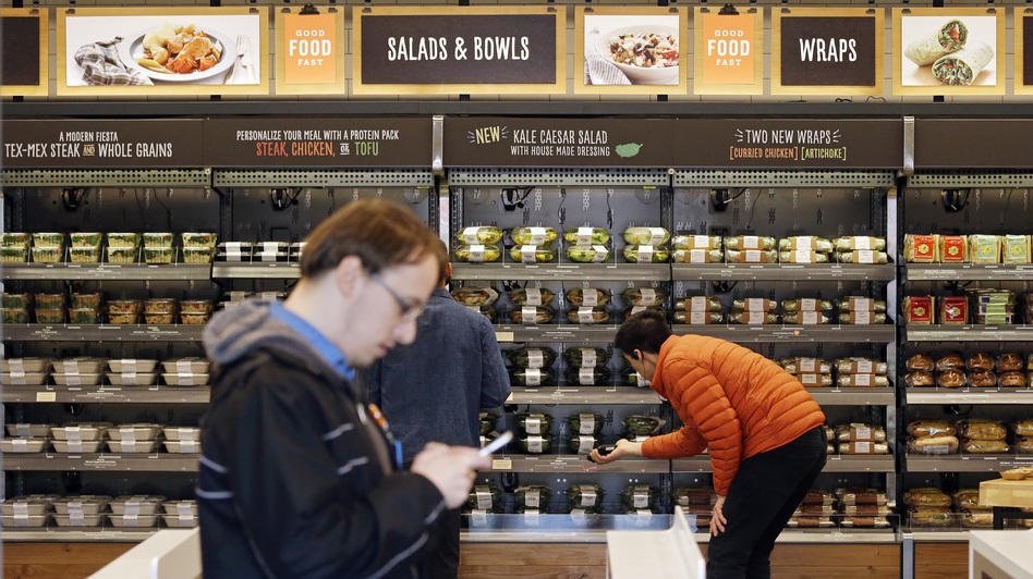 Shoppers roam through an Amazon Go store in April. The automated grocery, which had been restricted to Amazon employees, will be open to the public starting Monday. (Elaine Thompson/AP)
