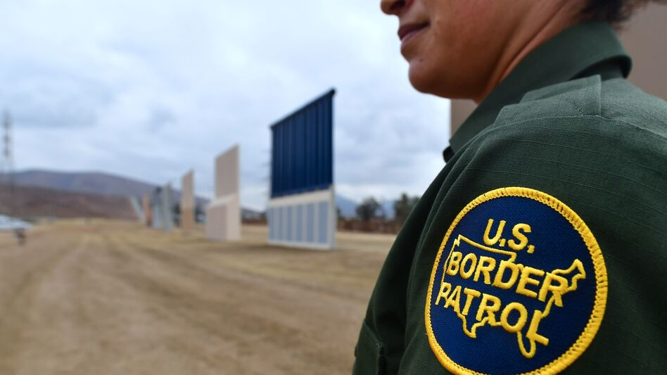 A U.S. Border Patrol officer stands near prototypes of President Trump's proposed border wall in San Diego last November. (Frederic J. Brown/AFP/Getty Images)