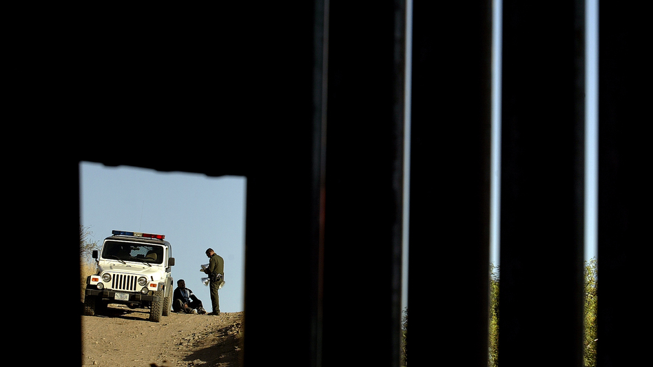 A U.S. Border Patrol agent questions a man in Nogales, Ariz., seen through a hole in a metal fence marking the border between the U.S. and Mexico, in 2007.