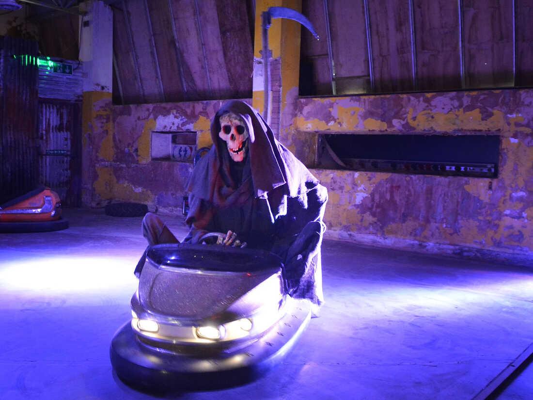 The Grim Reaper rides a bumper car.