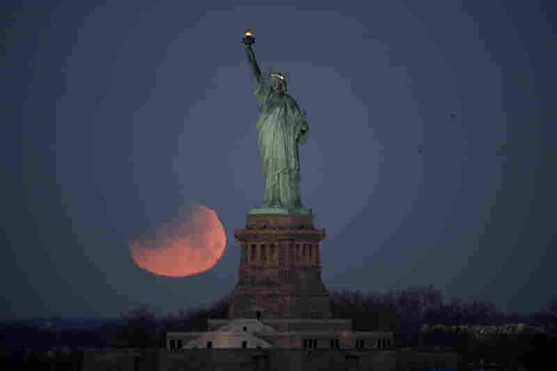 The Statue of Liberty is backdropped by a supermoon on Wednesday as seen from Brooklyn. The supermoon, which is the final of three consecutive supermoons, also experienced lunar eclipse as it set over the horizon, but only a partial eclipse was visible on the East Coast.