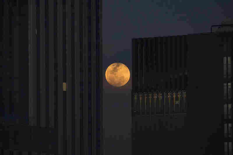 The moon rises between two office buildings in Bangkok.