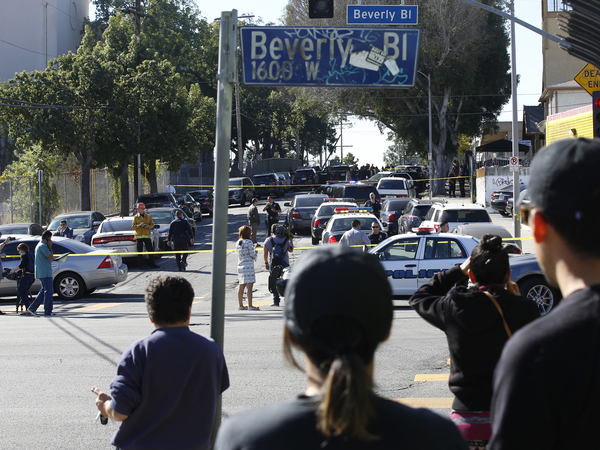 People wait for news about the shooting that left two injured at Salvador Castro Middle School in Los Angeles on Thursday.