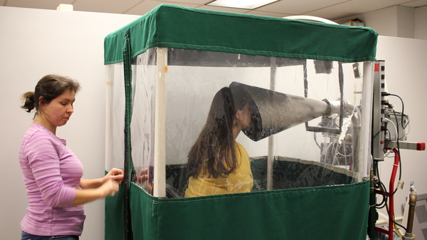 Undergraduate Shira Rubin gamely demonstrates the Gesundheit machine, which collects samples of virus from the breath that sick students exhale. Rubin helps Dr. Somayeh Youssefi (left) set up the machine before patients use it.
