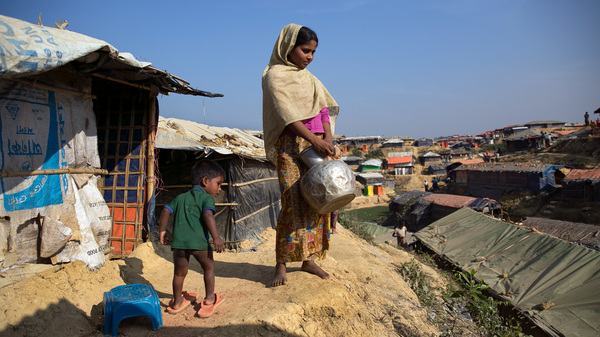 Sanura Begum stands with her son, Abdur Sobor, outside her plastic and bamboo shelter in the Kutupalong refugee camp in Bangladesh. One of the things she misses most about Myanmar is her family