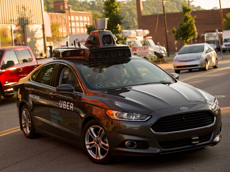 An Uber driverless Ford Fusion drives in Pittsburgh in 2016. On Friday, Uber and Google's Waymo self-driving unit announced a settlement in their trade secrets case. (Jeff Swensen/Getty Images)