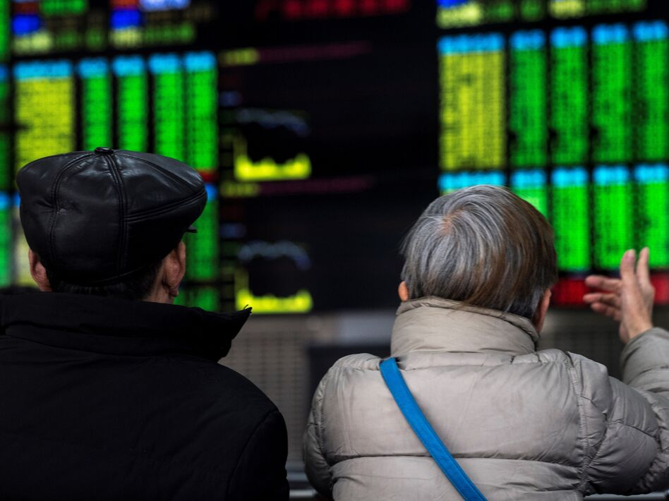 Two investors chat while keeping an eye on stock price movements shown on a screen at a securities company in Shanghai on Friday. (Johannes Eisele/AFP/Getty Images)