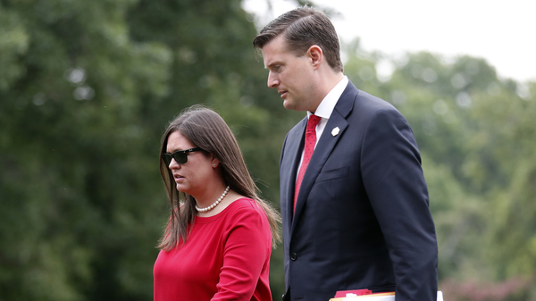 White House press secretary Sarah Huckabee Sanders with then-staff secretary Rob Porter in August. In the wake of Porter's resignation, Sanders has reassured reporters that President Trump is sympathetic to victims of domestic abuse.