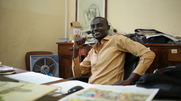 "Didier Kassai uses comics to ""transmit a message."" His father opposed to a career in art until Kassai began earning money for his drawings. Here he sits in his office in Bangui, capital of the Central African Republic."