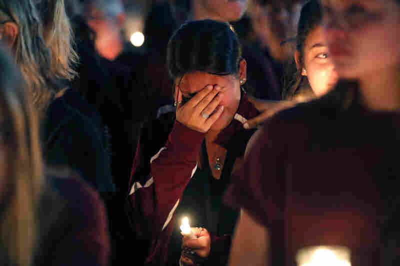 A woman cries during a candlelight vigil Thursday for the victims of the Wednesday shooting at Marjory Stoneman Douglas High School, in Parkland, Fla.