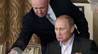 In this Nov. 11, 2011, file photo, Yevgeny Prigozhin, left, serves food to then-Russian Prime Minister Vladimir Putin during dinner at Prigozhin's restaurant outside Moscow, Russia. Friday, Prigozhin, along with 12 other Russians and three Russian organizations, was charged by the U.S. government as part of a vast and wide-ranging effort to attack the 2016 U.S. presidential election.