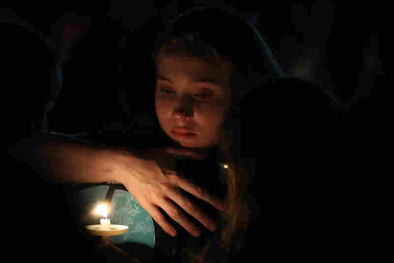 A young girl clutches a friend during Thursday night's vigil in Parkland.