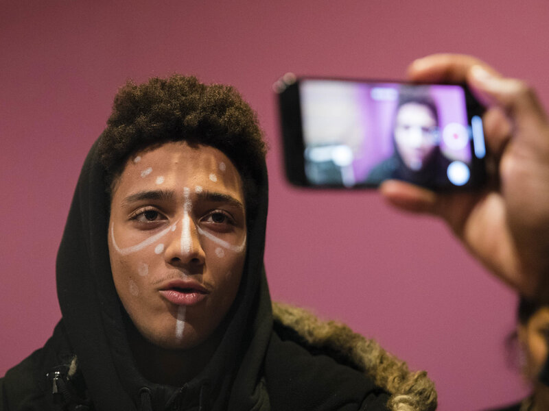 Jayden Pontes, 17, a student from Boston Arts Academy, is filmed wearing face paint similar to characters from Black Panther during a discussion of the significance of the film's release in Boston on Wednesday. The students planned to wear the face paint to the film's screenings.     Boston Globe/Boston Globe via Getty Images
