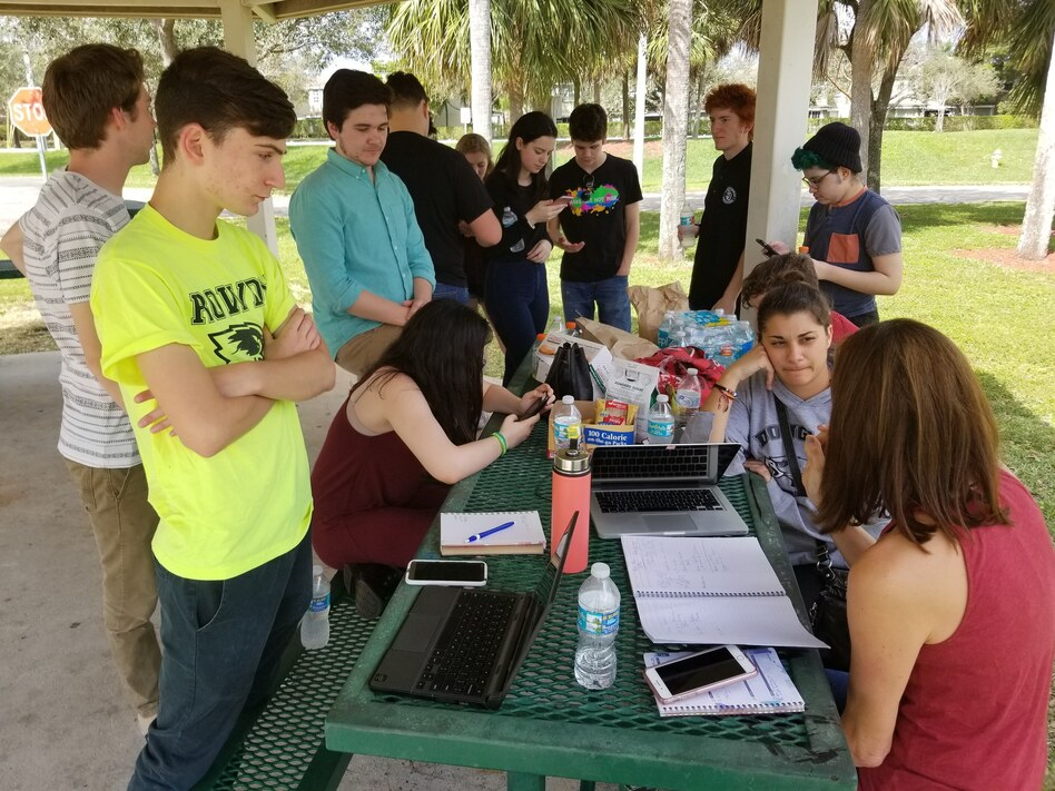 Students from Marjory Stoneman Douglas High School use a picnic table at a city park as a media center to plan their rallies on Washington, D.C., and around the country. (Brian Mann/North Country Public Radio)