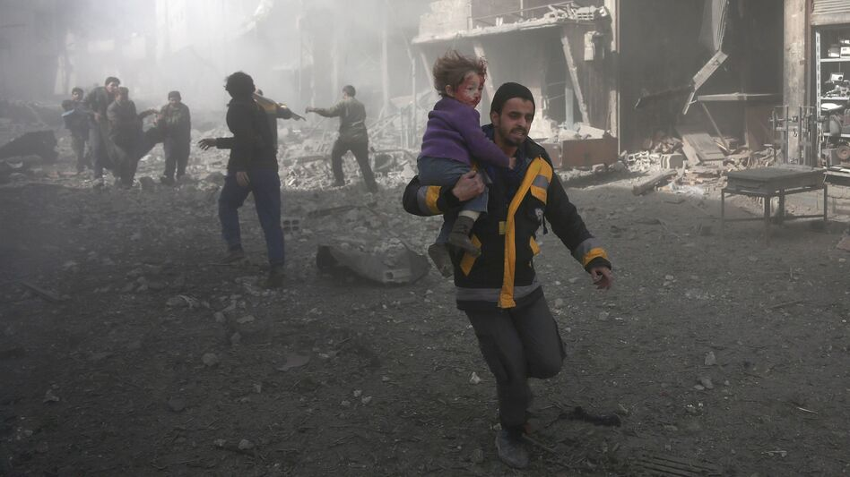 A Syrian man carries a child injured in the government bombing of eastern Ghouta, on the outskirts of Damascus on Monday. (Abdulmonam Eassa/AFP/Getty Images)