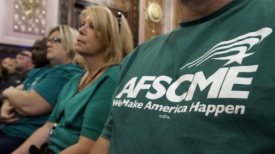Members of the American Federation of State County and Municipal Employees union, or AFSCME, listen to a council executive speak about conditions at state prisons and detention centers in Illinois. (Seth Perlman/AP)