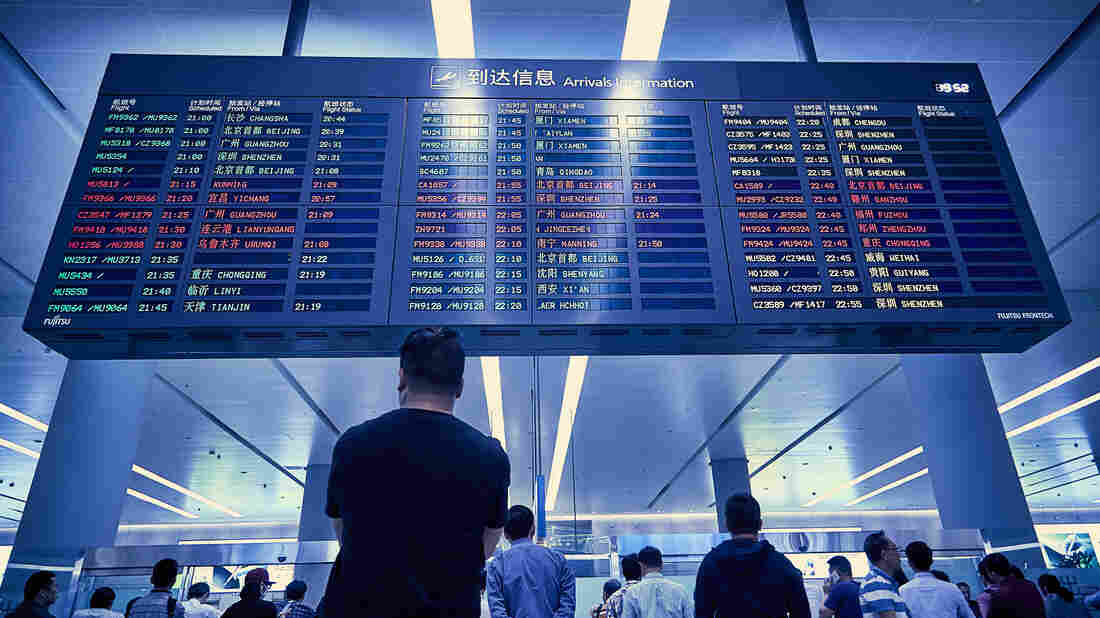 People waiting at an airport arrivals and departure board