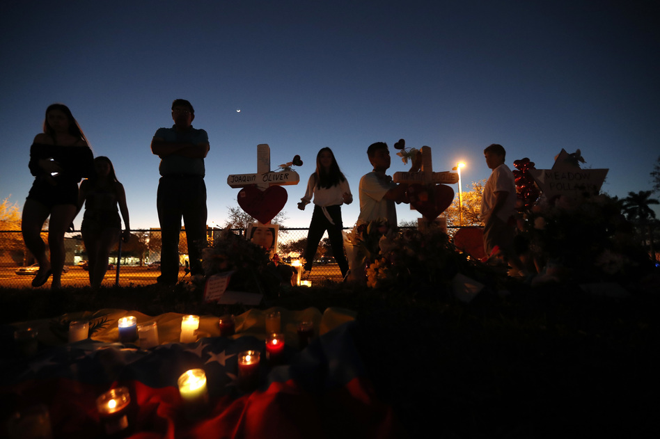 People visit a makeshift memorial outside Marjory Stoneman Douglas High School in Parkland, Fla., where 17 students and faculty were killed in a mass shooting on Feb. 14. (Gerald Herbert/AP)