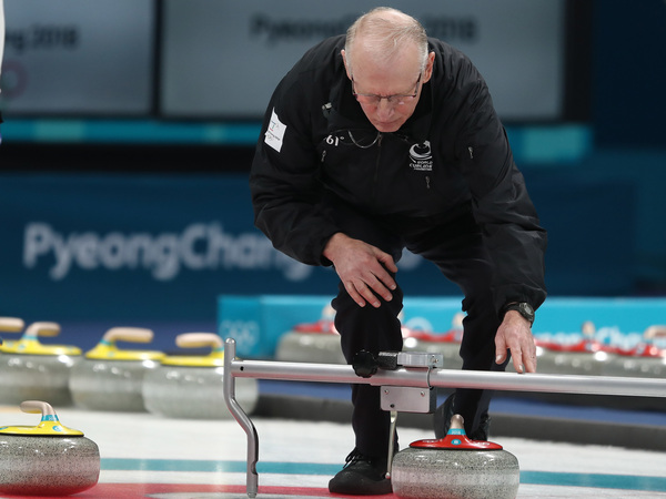 A curling official checks the distance between stones during the gold medal between the United States and Sweden at the Pyeongchang 2018 Winter Olympic Games.