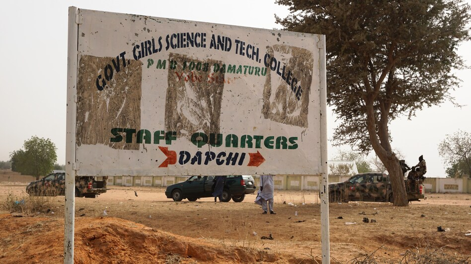 Soldiers drive past a sign leading to the Government Girls Science and Technical College staff quarters in Dapchi, Nigeria, on Thursday. Scores of schoolgirls have been reported missing in Monday's suspected Boko Haram attack. (AMINU ABUBAKAR/AFP/Getty Images)