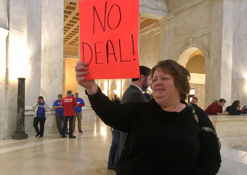 """Special needs teacher's aide Belva Perry holds up a sign on Wednesday at West Virginia's Capitol that reads """"no deal."""" (John Raby/AP)"""