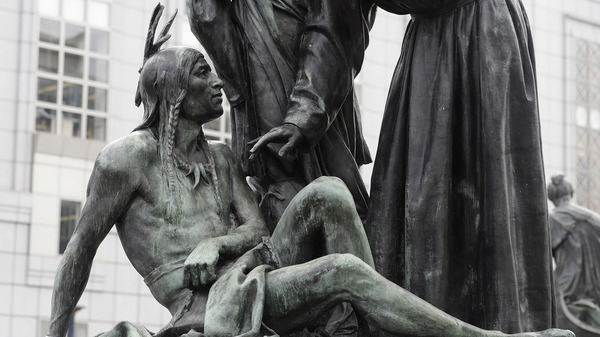 A statue of a Native American sitting below Sir Francis Drake and Father Junipero Serra in San Francisco.