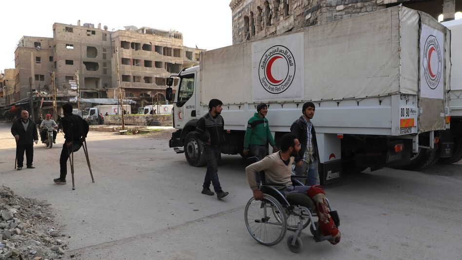 A convoy of Syrian Red Crescent trucks arrives in Douma, in the Syrian rebel-held enclave of Eastern Ghouta, on Monday. This aid convoy is the first to reach the besieged area in weeks. (Amer Almohibany/AFP/Getty Images)
