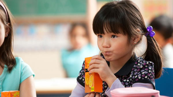 A young girl drinks juice from a box. Because of layers of material that can be difficult to separate, many containers for juices and broths have traditionally been destined for landfills. But recycling them is getting easier.