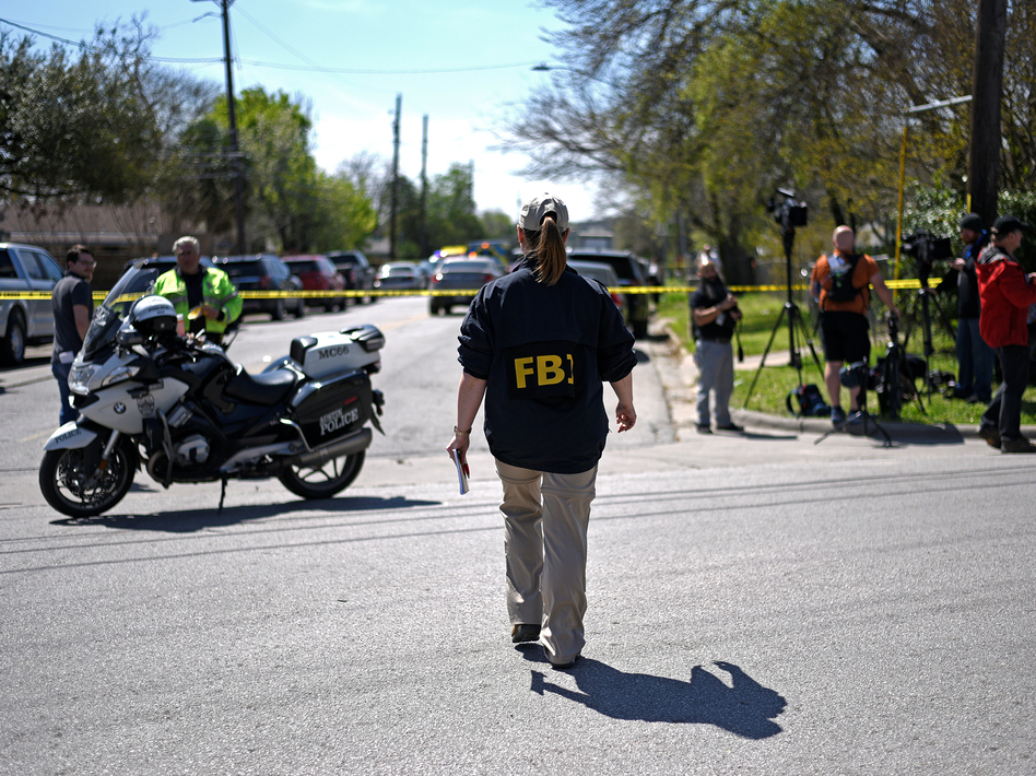 An FBI agent walks toward the scene of one of the blasts in Austin on Monday. (Sergio Flores/Reuters)