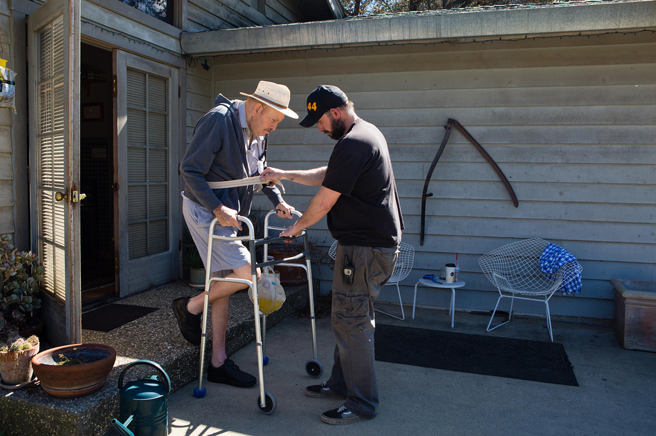 Leon Beers, a retired railroad engineer who lives near Sacramento, Calif., has a form of Parkinson's disease. His live-in caregiver, Timothy Wehe, helps him get outside using a walker.