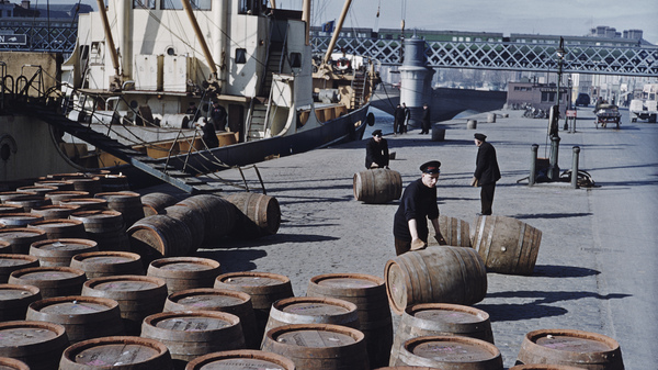 Workers roll barrels of Guinness in June 1955 on a quayside in Dublin.