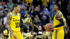 Jairus Lyles, left, and teammate Jourdan Grant of the UMBC Retrievers react Friday night to their 74-54 victory over the Virginia Cavaliers in Charlotte, N.C.