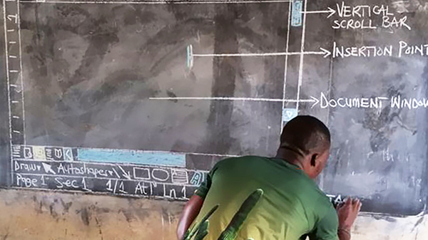 Owura Kwadwo Hottish illustrates a window of Microsoft Word using colored chalk on a blackboard for his students at the Betenase M/A Junior High School in Kumasi, Ghana.