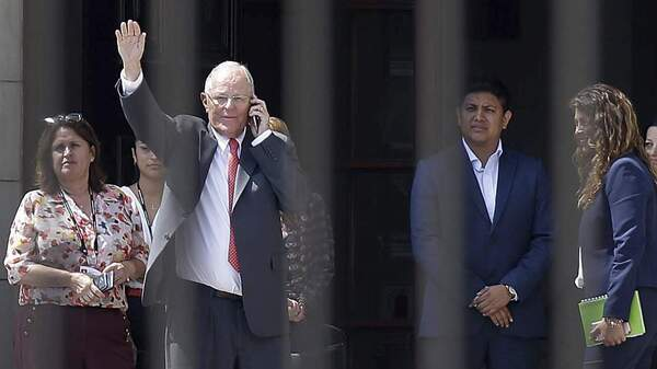 Peruvian President Pedro Pablo Kuczynski waves from the governmental palace in Lima on Wednesday, shortly after the embattled leader offered his resignation to lawmakers ahead of a scheduled vote on whether to impeach him.