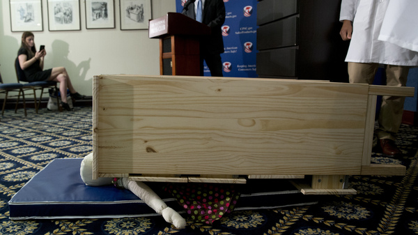A child-size dummy is crushed by a dresser during a Consumer Product Safety Commission news conference in Washington, D.C., in 2016. That year Ikea began a recall of millions of dressers after six children were killed in tip-over incidents. But a new study says that tip-over risks extend far beyond any one furniture-maker.
