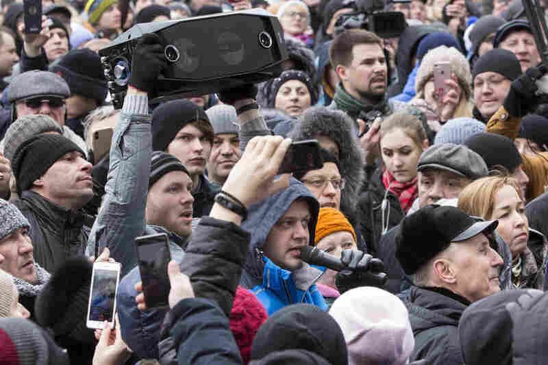 A man speaks into a microphone in the crowd gathered Tuesday to pay respects to the victims of a shopping center fire in the Siberian city of Kemerovo, about 2,000 miles east of Moscow.