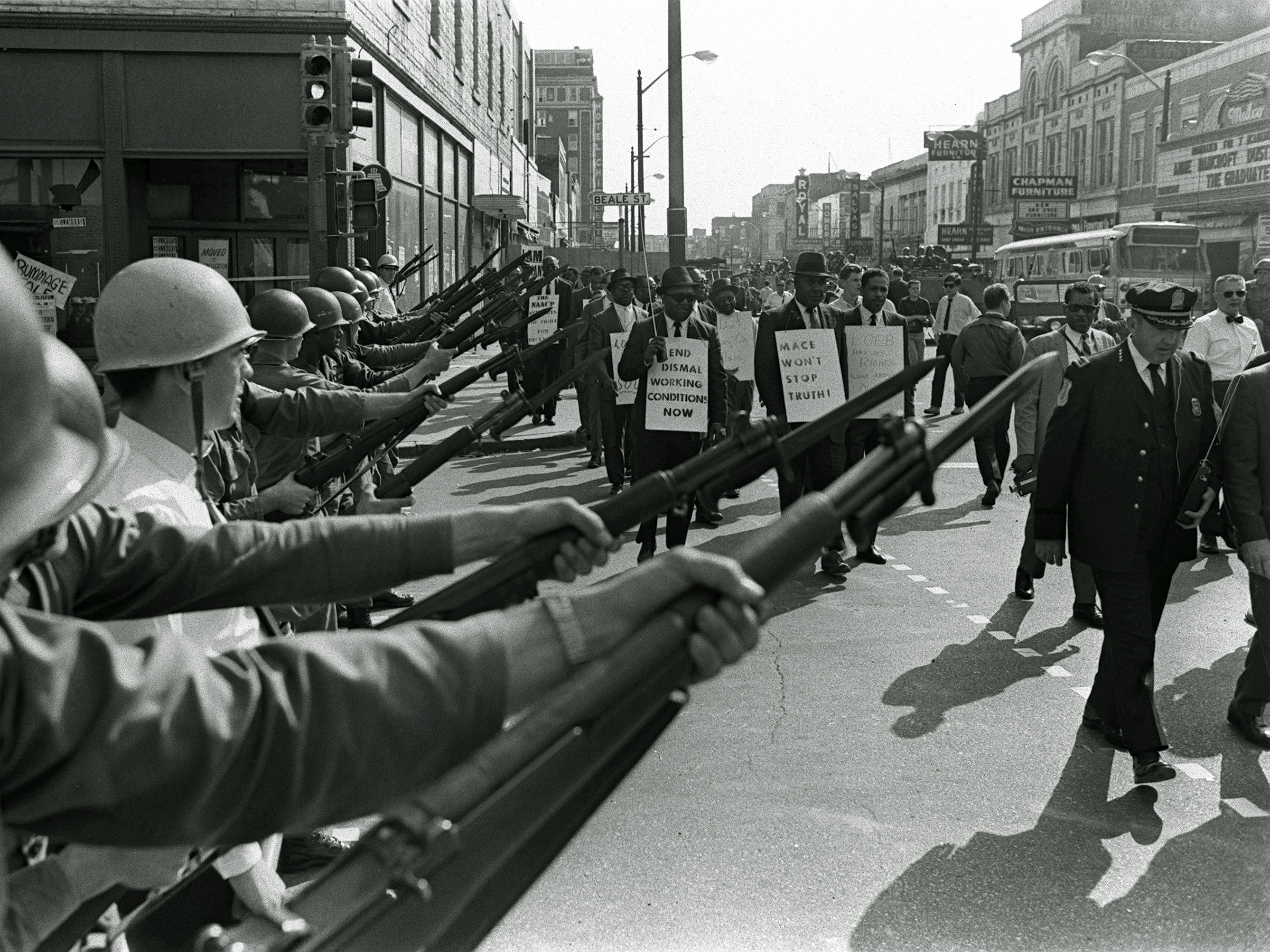 Striking Memphis sanitation workers march past Tennessee National Guard troops with fixed bayonets during a 20-block march to City Hall on March 29, 1968. Some 3,800 National Guard troops rolled into the city in armored tanks after the Tennessee legislature enacted a state of emergency.