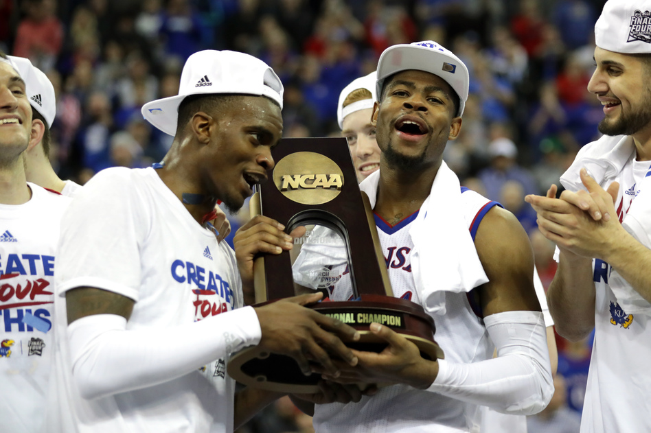 Lagerald Vick (left) and Malik Newman (right) of Kansas celebrate with the regional championship trophy after defeating Duke in the Midwest Region. (Streeter Lecka/Getty Images)