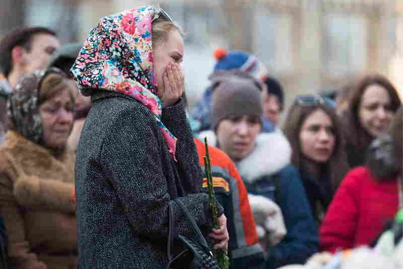People gather outside the Zimnyaya Vishnya (Winter Cherry) shopping center to pay tribute to the victims of a fire that engulfed the mall on Sunday, killing at least 64 people. The building's alarm system reportedly had been shut off.