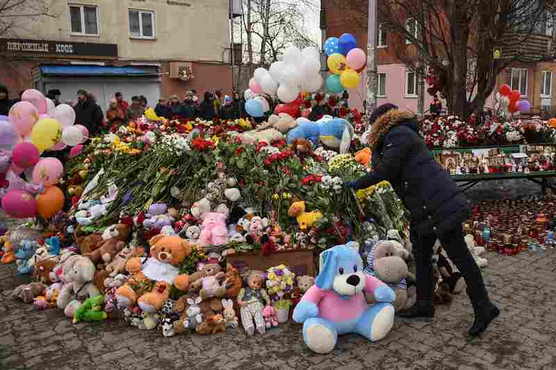 People lay flowers at a makeshift memorial in tribute to the victims of the fire.