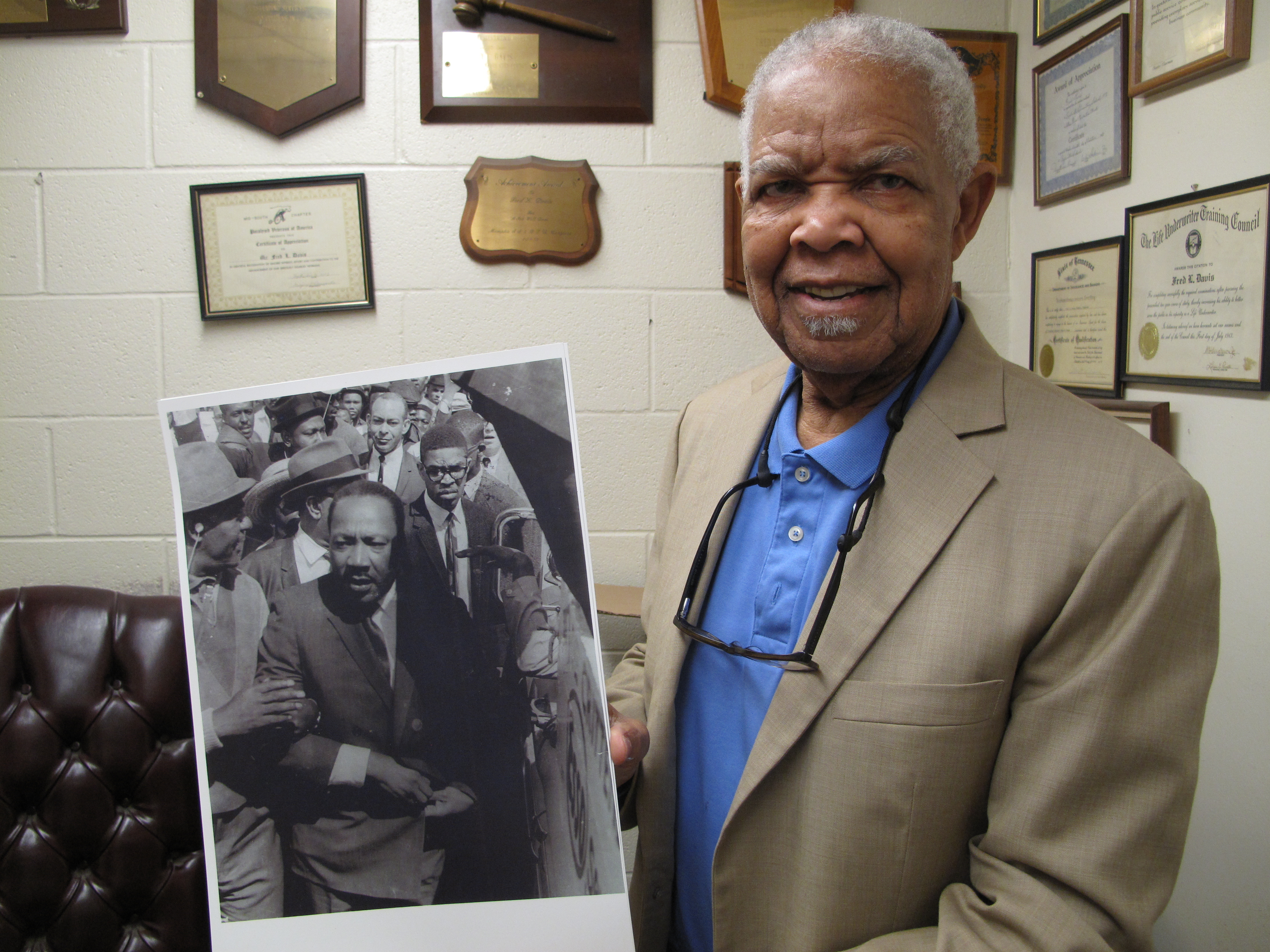 Fred Davis, a former Memphis city councilmember, holds a photograph taken on March 28, showing him standing near King with a crowd following behind.