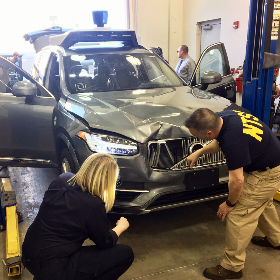 A photo provided by the National Transportation Safety Board shows investigators examining the self-driving Uber SUV that fatally struck a woman in Tempe, Ariz., this month. (AP)