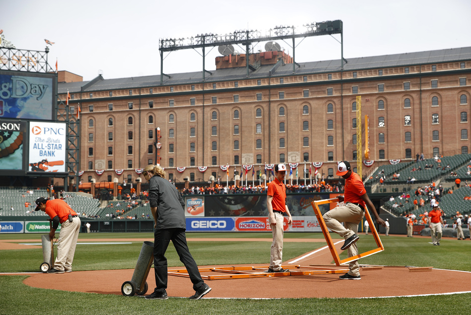 Groundskeepers prepare the infield before an opening-day baseball game between the Minnesota Twins and the Baltimore Orioles on Thursday in Baltimore. (Patrick Semansky/AP)