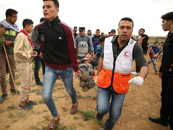 A Palestinian youth is carried on a stretcher Friday after being injured during a demonstration near the border with Israel east of Jabalia in Gaza.