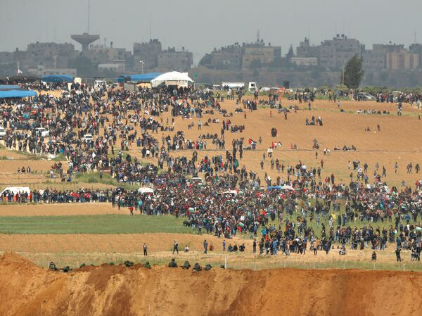 "From the southern Israeli kibbutz of Nahal Oz, Palestinians can be seen participating in the ""March of Return"" protests, under the alert eyes of Israeli soldiers, in the foreground."