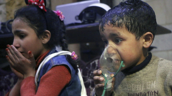 This image released early Sunday by the Syrian Civil Defense White Helmets, shows a child receiving oxygen through respirators following an alleged poison gas attack in the rebel-held town of Douma, near Damascus, Syria.