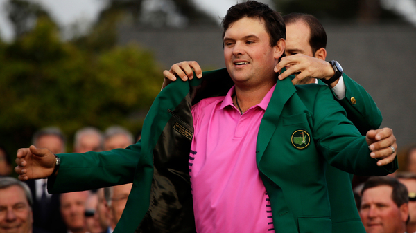Former Masters champion Sergio Garcia, of Spain, helps Patrick Reed with his green jacket after winning the Masters golf tournament Sunday in Augusta, Ga.