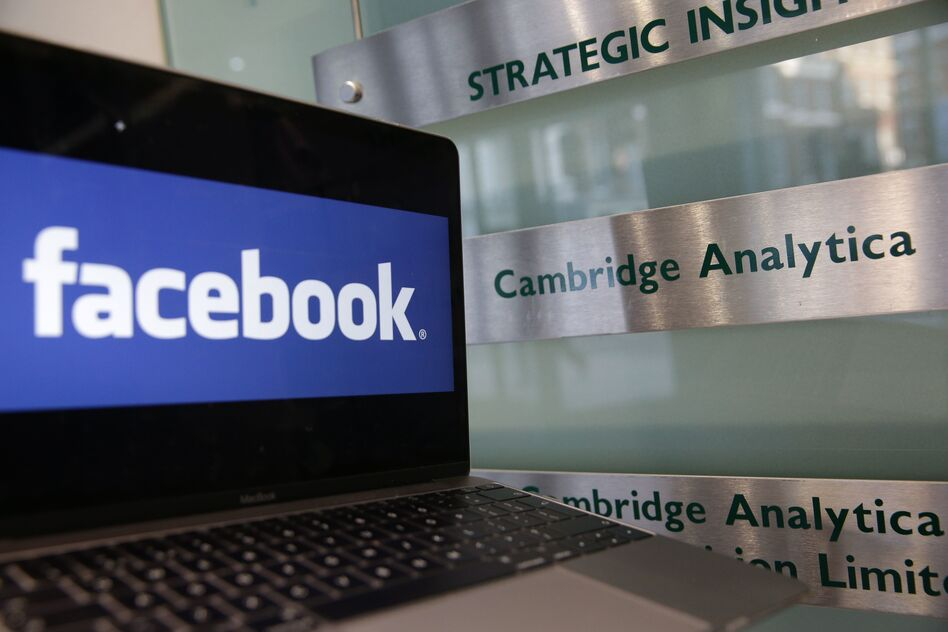 A laptop showing the Facebook logo is held alongside a Cambridge Analytica sign at the entrance to the London offices of Cambridge Analytica. The company's acting CEO, Alexander Tayler, is stepping down, and is the second CEO out since the data sharing scandal broke. (Daniel Leal-Olivas/AFP/Getty Images)